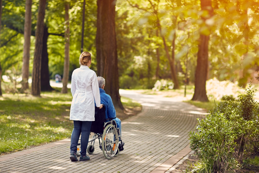 One of Elite Specialty Staffings wonderful travel nurses takes a patient for an afternoon walk through a beautiful wooded park where the patient can enjoy time outside of one of our partner healthcare hospital facilities from the PACU or Post Anesthesia Care Unit