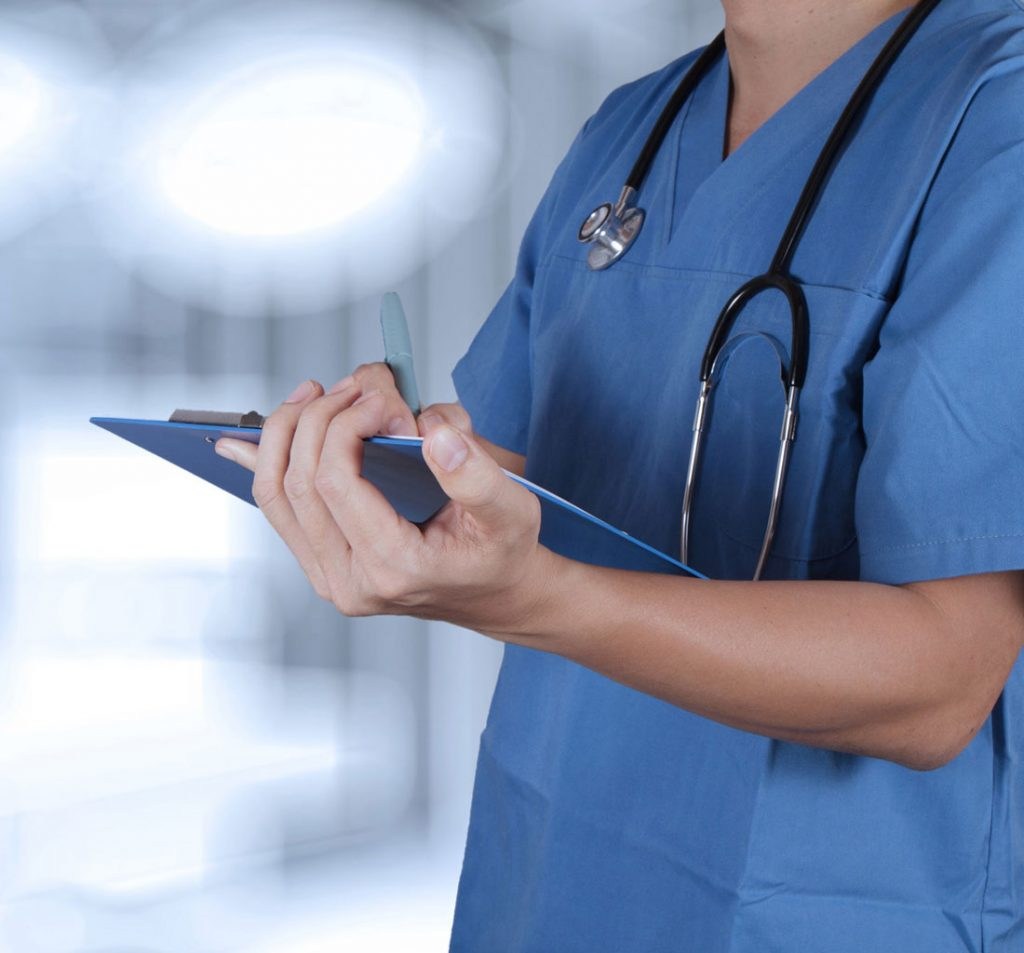 A male Elite Specialty Staffing travel nurse in blue scrubs with a stethoscope around his neck works diligently in the hallway of a facility where many NICU or Neonatal Intensive Care Unit patients arrive into this world